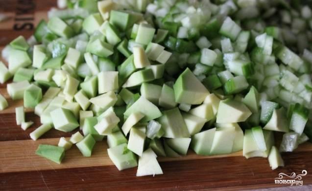 Авокадо и огурцы помойте и очистите. Нарежьте их кубиками и добавьте в суп.
