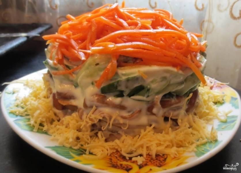 Верхушку салата украсьте корейской морковью. Сбоку присыпьте тертым сыром. Поместите форму с салатом в холодильник на несколько часов. Затем аккуратно удалите форму и подавайте салат к столу. Приятного аппетита!