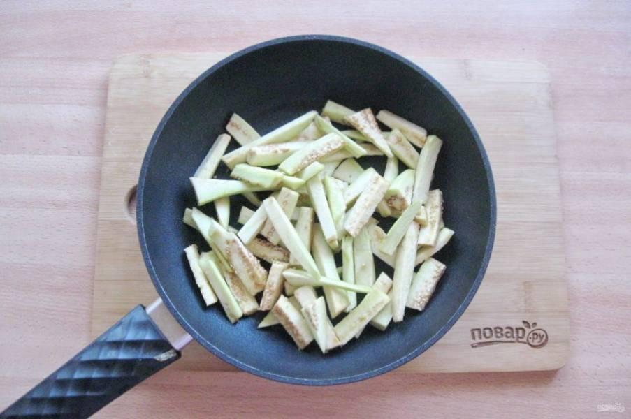 Баклажан помойте, очистите и нарежьте брусочками. Выложите в сковороду.