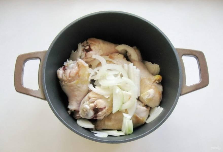 Влейте подсолнечное масло и обжарьте голени до легкого золотистого цвета. Репчатый лук очистите, помойте и нарежьте. Добавьте к голеням. Тушите лук с курицей, помешивая в течение 10 минут.