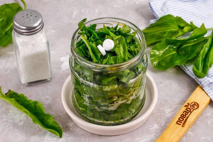 Добавьте еще треть щавеля и снова примните, присыпьте солью. Выложите оставшуюся массу зелени и добавьте 2 таблетки аспирина. Аспирин предотвратит брожение, заготовка останется свежей в течение 4-5 месяцев, но только при хранении на холоде!