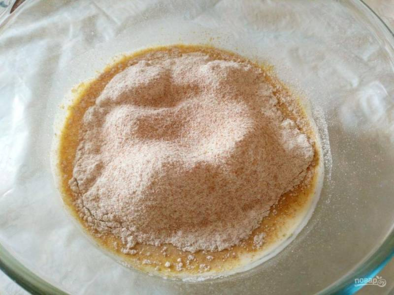 Добавьте в жидкую смесь соль и просеянную цельнозерновую муку, перемешайте.