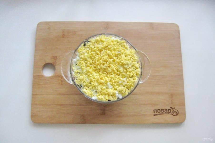 Желтки натрите на терке и выложите на белки.