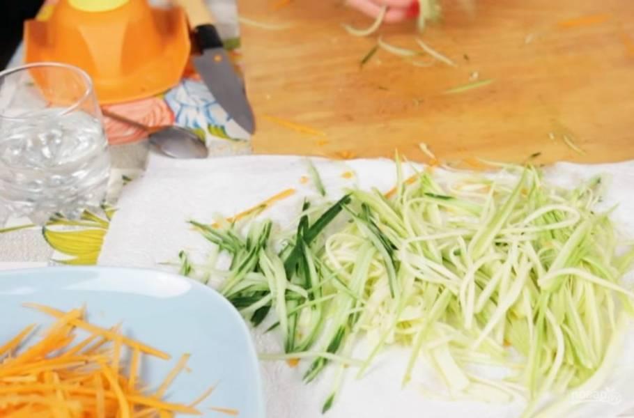 1. Для начала нарежьте соломкой морковь, огурец и цукини. Можете не очищать их от шкурки, чтобы салат был максимально цветным. Выложите овощи на полотенце, чтобы с них стек сок.
