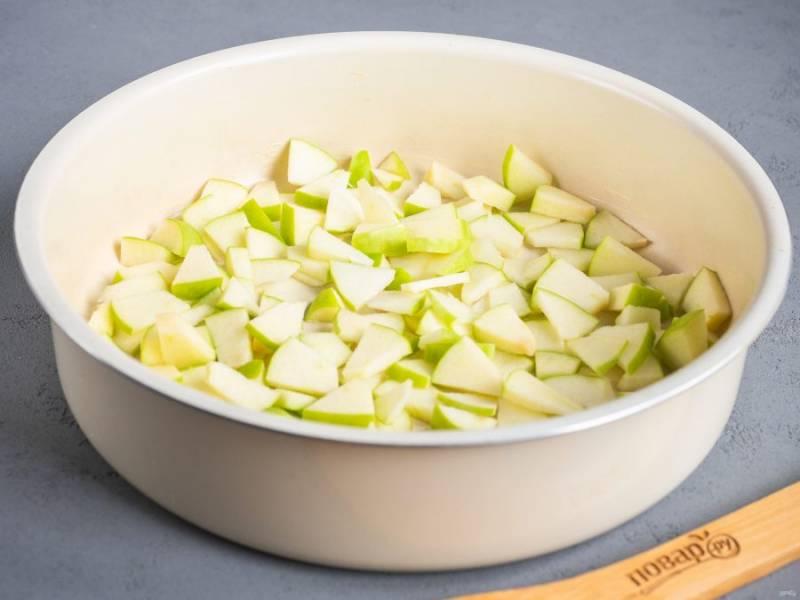 Форму (24-26 см.) смажьте небольшим кусочком сливочного масла. Яблоки нарежьте небольшими кусочками и выложите на дно формы.
