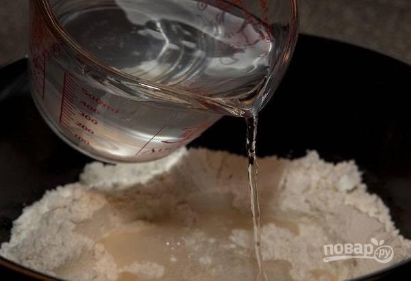 2. В глубокую мисочку просейте примерно половину муки и влейте воду.