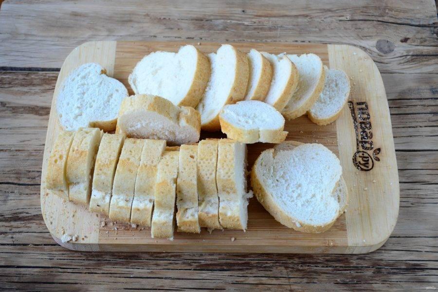 Багет нарежьте на кусочки толщиной 8-10 мм.