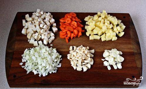 Во время приготовления фасоли следует заготовить овощи. Корень сельдерея и картофель и лук нарежьте кубиками. Морковь порезать полумесяцами, чеснок измельчить.