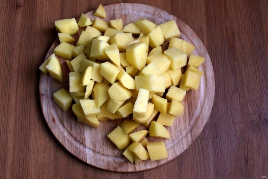 Поставьте на огонь кастрюлю с водой. Когда вода закипит, опустите нарезанный кубиками картофель. Дайте ему повторно закипеть и снимите пену. Варите 5 минут.