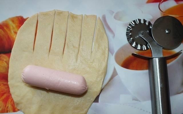 Берем одну часть теста и скатываем в шарик. Раскатываем в лепешку. На одну половинку лепешки кладем сосиску, а вторую разрезаем на полоски.