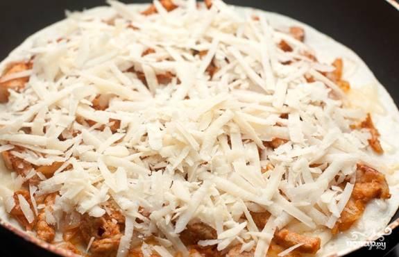 4.Приступайте к оформлению кесадильи. На сухую нагретую сковороду положите тортилью, сверху насыпьте тертый сыр. Добавьте начинку, накройте тертым сыром, уложите сверху вторую лепешку.