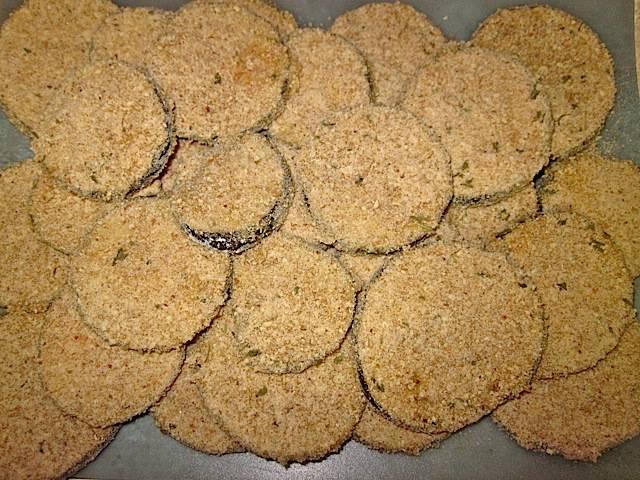 Обмакните баклажаны в яйцо, а затем в панировочные сухари, смешанные с пармезаном и специями.