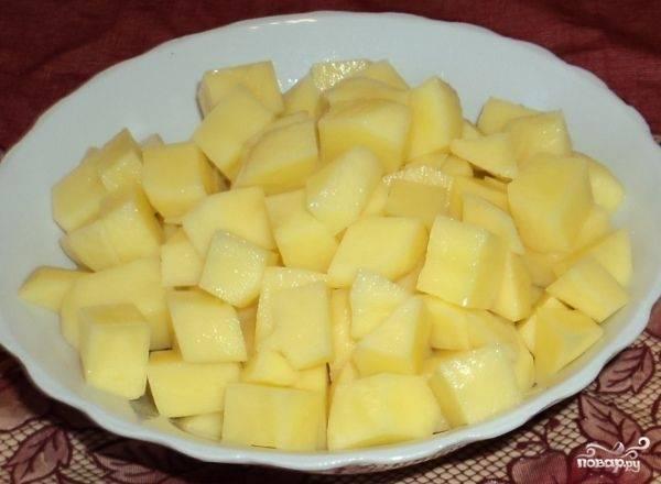 Чистим картофель и нарезаем кубиками. Наливаем в кастрюлю примерно 2 л воды и ставим варить картошку.