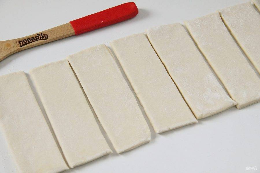 Тесто раскатайте в одном направлении и нарежьте полосками, должно получиться 8 штук, шириной соответствующей ширине половины сосиски.