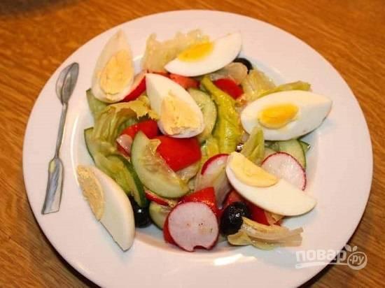 Выкладываем перемешанные и заправленные маслом овощи на тарелку. Яйцо нарезаем на дольки и выкладываем поверх овощей.