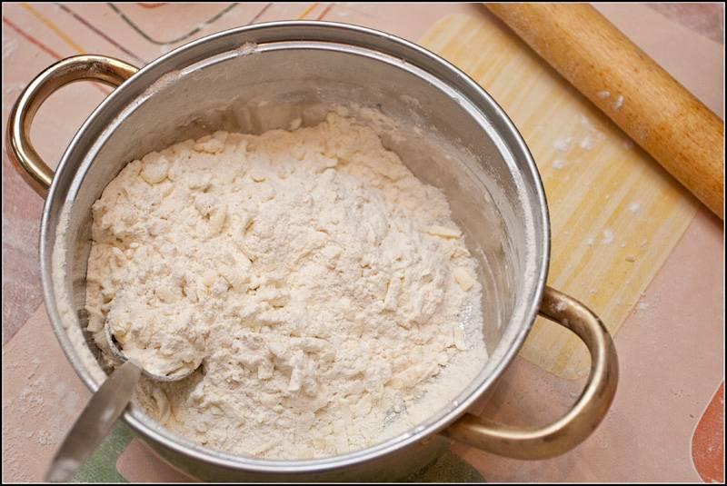 2. Добавить просеянную муку со щепоткой соли. Начать активно перемешивать. Воду в рецепт приготовления пирога со смородиной и творогом лучше использовать также очень холодную, буквально ледяную. Влить постепенно немного воды, замешивая тесто. Оно должно получиться мягким и очень эластичным.