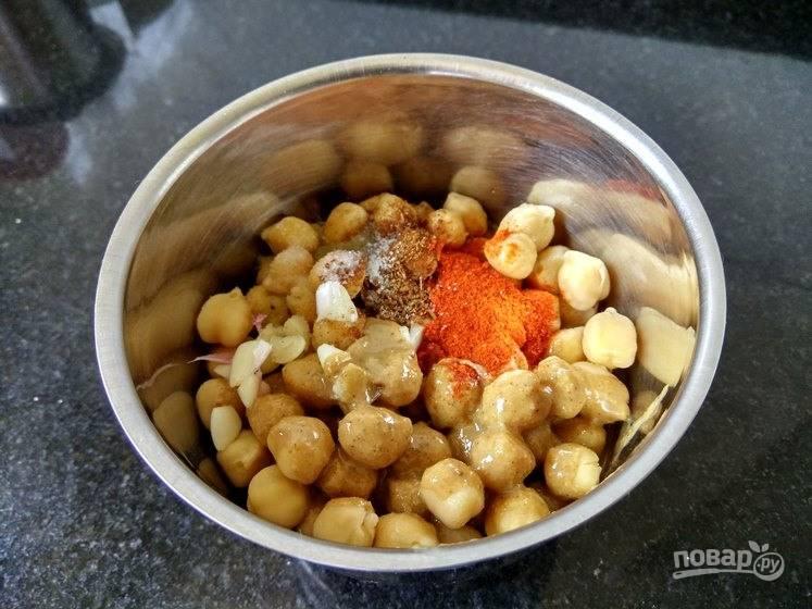 2. Отварите его до готовности. Поместите нут в комбайн, добавьте воду, чеснок, чили, зиру, оливковое масло, лимонный сок и соль.