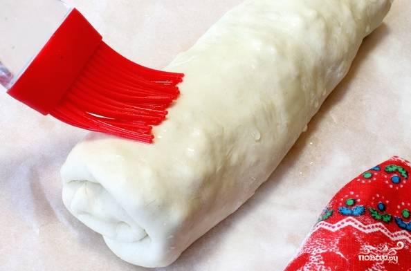 6. Дальше есть два варианта, как приготовить пирог с брынзой из слоеного теста: можно отправить запекаться его в таком виде или выбрать закрытый (то есть свернуть аккуратно рулетом или накрыть вторым пластом теста), например. Смажьте сверху немного растительным маслом и отправьте пирог в духовку.