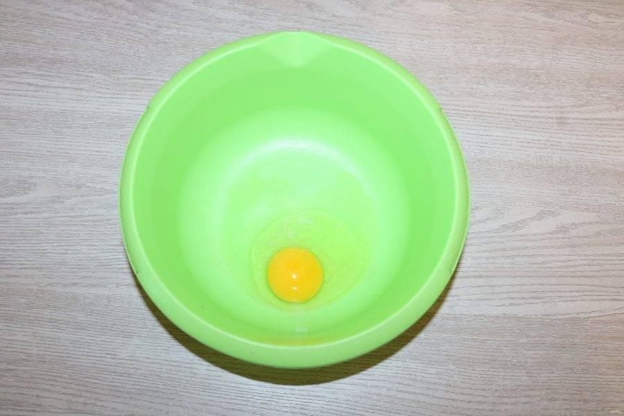Приготовьте тесто для токмача. В миску вбейте яйцо.