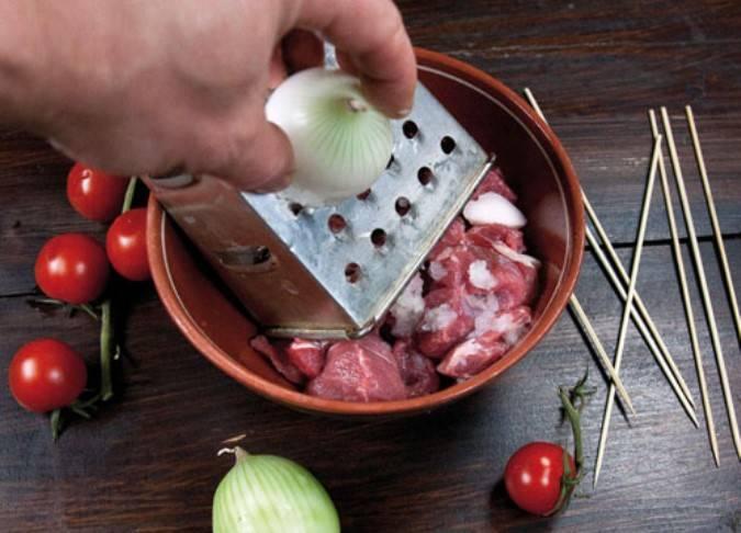 Сложите мясо и сало в миску, сверху потрите две луковицы.