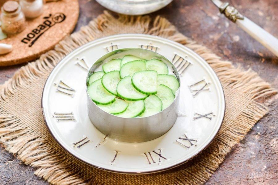 Свежий огурец нарежьте тонкими пластинами, выложите следующим слоем в салат.