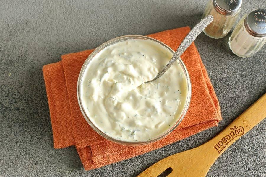 Для соуса соедините сметану и майонез в равных пропорциях. Добавьте оставшийся чеснок и измельченный укроп. Перемешайте.