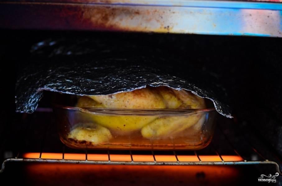 Запеките курицу в разогретой на 250 градусов духовке 15-20 минут. Достаньте, положите к ней в форму для выпекания чеснок и запекайте, укрыв фольгой, ещё 30 минут.