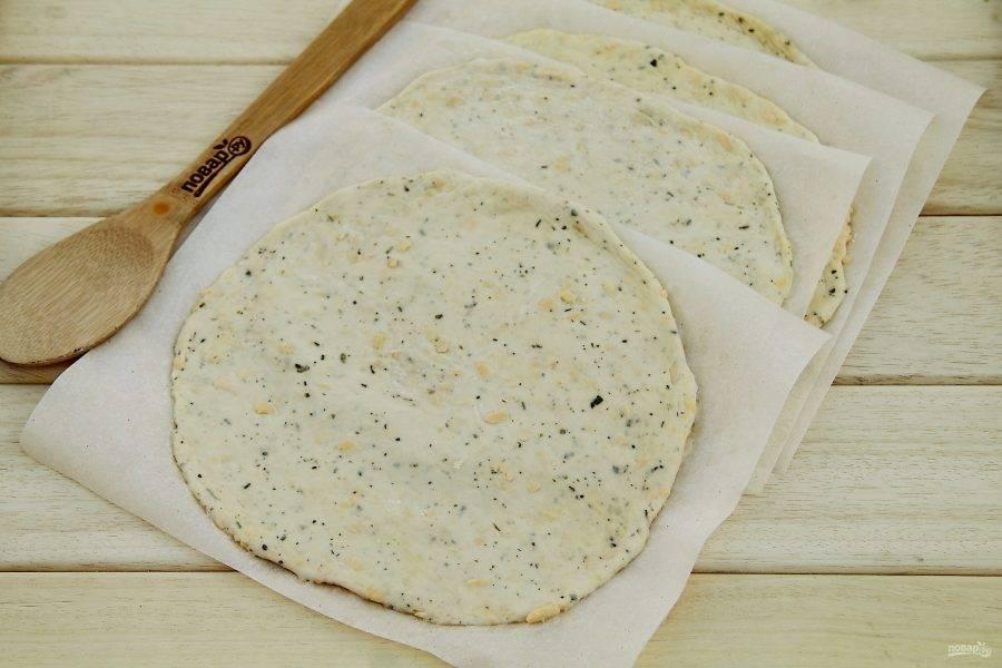Подошедшее тесто необходимо обмять и разделить на 4 части. Из каждой части раскатайте лепешку, толщиной 4-5 мм., затем присыпьте лепешки хорошенько мукой и переложите листами пергамента.