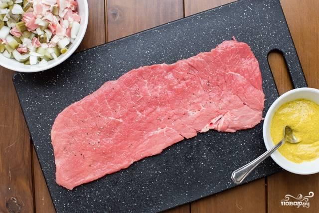 Приготовьте начинку. Солёные огурцу, бекон и одну половинку лука мелко нарежьте. Отбейте кусочки свинины (если они ещё не отбиты). Поставьте рядом горчицу.