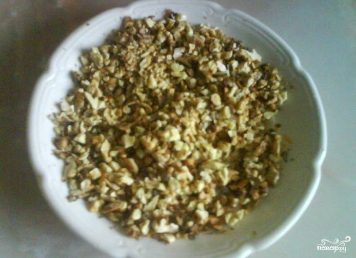 Обжарьте колотые грецкие орехи на сухой сковороде. Пропустите их через мясорубку, истолките в ступке пестиком или же измельчите при помощи блендера.