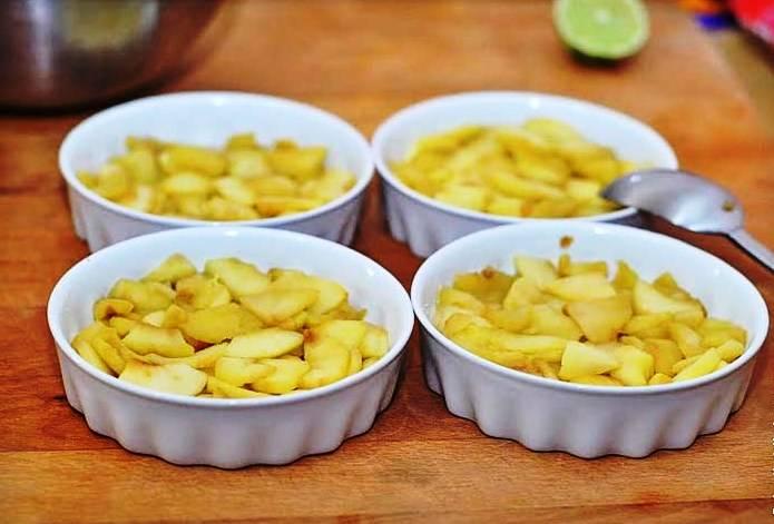 Формочки для запекания смажьте маслом и наполните наполовину яблоками. Сверху выложите тесто и выпекайте в течение 45 минут при 140 градусах. Подавайте на стол в теплом виде.