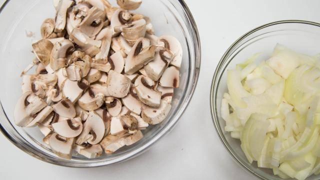 2. Соль, перец и сушеную петрушку смешайте в маленькой мисочке. Грибы промойте, просушите бумажным полотенцем и нарежьте пластинками. Лук почистите и нарежьте полукольцами.