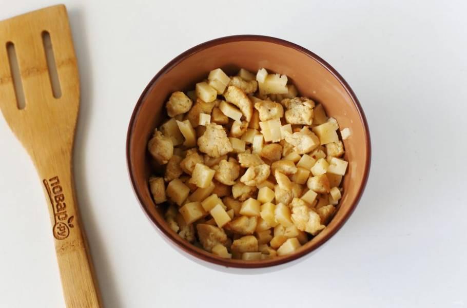 Для начинки нарежьте куриное филе небольшими кубиками и обжарьте с солью и специями в сковороде. Охладите и добавьте нарезанный кубиками сыр.