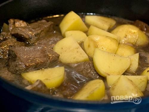 5. Добавьте к мясу картофель, морковь, чеснок и грибы. Приправьте перцем, лавровым листом и соусом. Тушите все под крышкой до полуготовности картофеля.