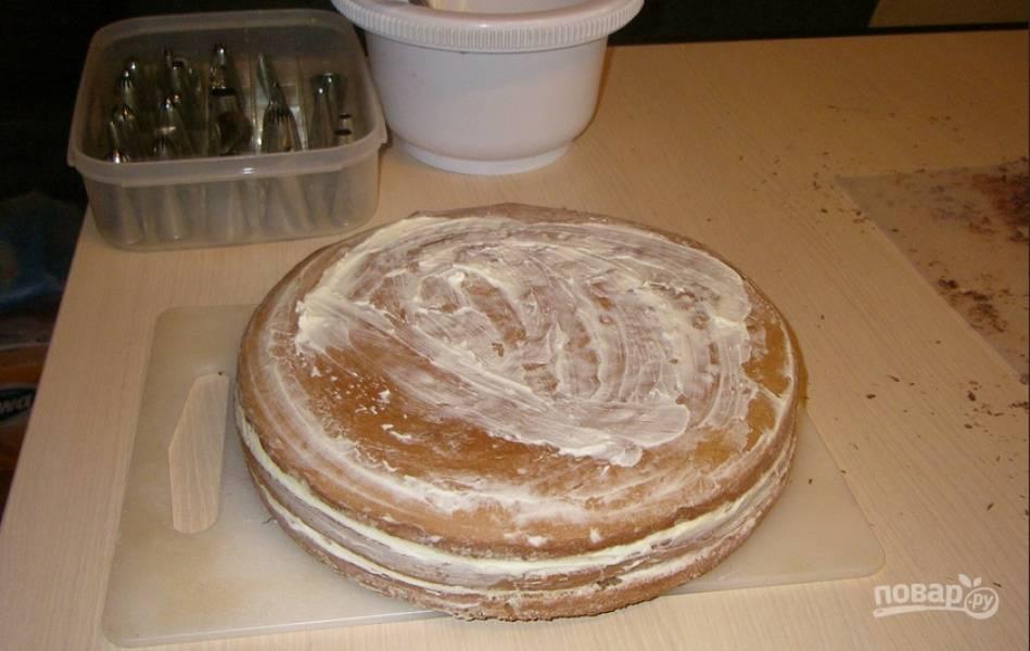5. Проделываем все то же со всеми коржами, а затем остатками крема смажем торт по бокам и сверху, чтобы украшение торта плотно держалось.