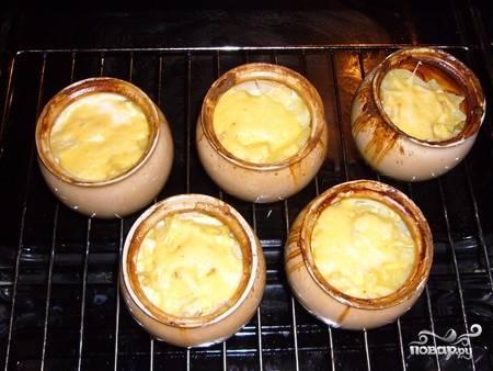 За 5 минут до готовности выкладываем в каждый горшочек горсть тертого сыра. Когда блюдо будет готово, посыпаем его свежей зеленью и подаем к столу.