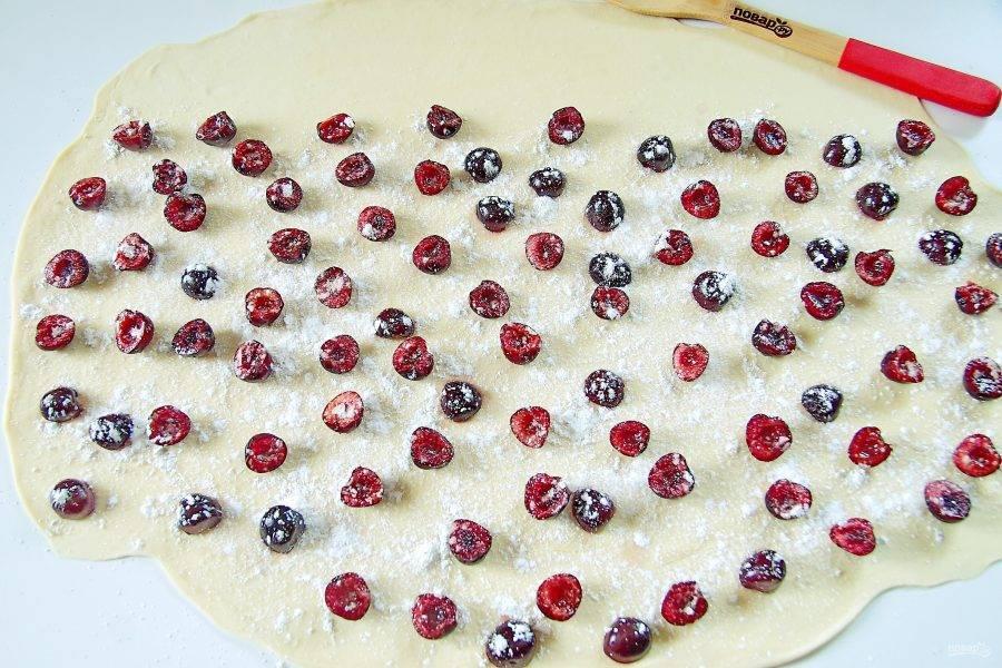 7. Слегка присыпьте стол мукой и раскатайте тесто в очень тонкий и прозрачный пласт, можно слегка потянуть его руками. На раскатанное тесто выложите равномерно начинку, отступив немного от одного края. Посыпьте ягоды крахмалом и сахаром.