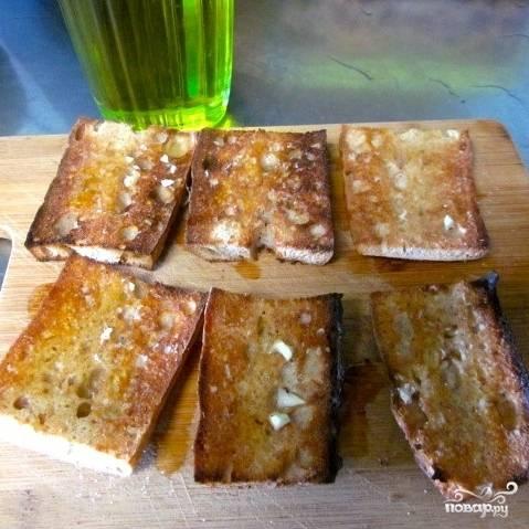 Ломтики хлеба подсушиваем на сухой сковороде или в тостере, затем натираем чесноком и слегка сбрызгиваем оливковым маслом.