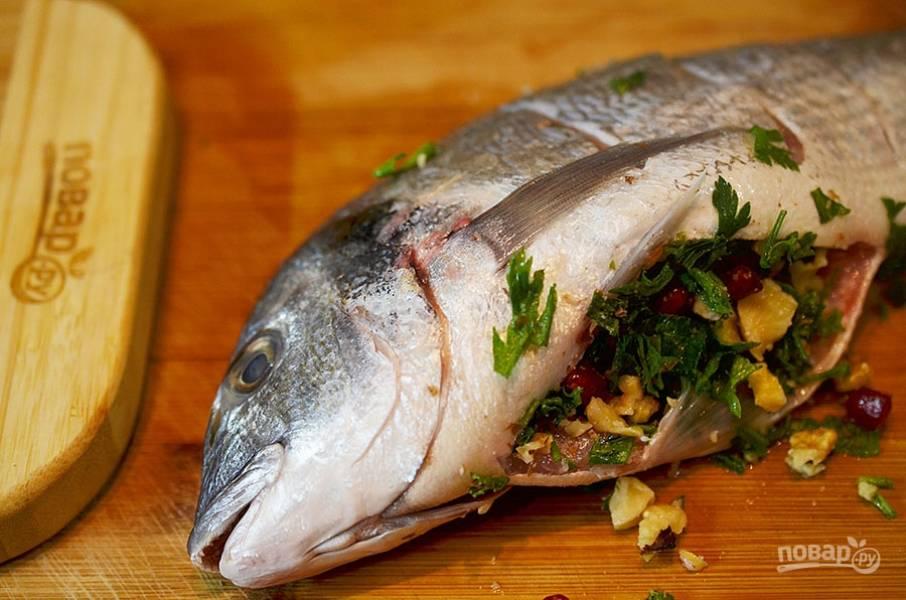 7. В брюшко рыбы положите начинку (часть оставьте для посыпки).