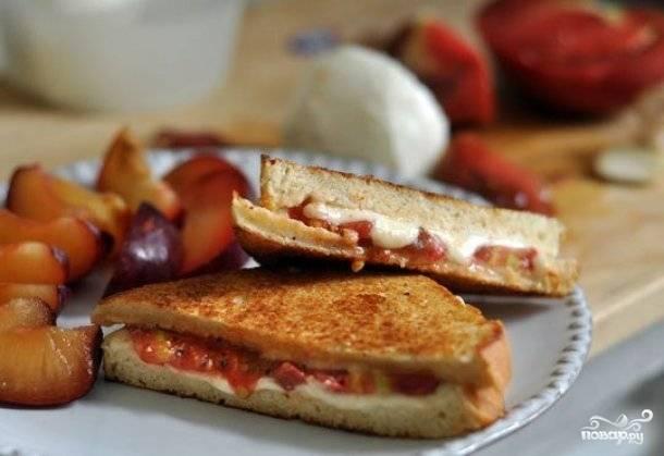 Сверху положите второй кусочек хлеба. Немного прогрейте бутерброд на сковороде, прижимая верхний кусочек хлеба, чтобы он склеился с нижним при помощи расплавленного сыра. Подавайте бутерброды горячими.