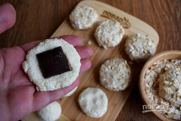 Из каждого шарика сформируйте лепешку на ладошке, положите в центр квадратик шоколада, залепите края. Сформированные сырники обваляйте в овсяных хлопьях.