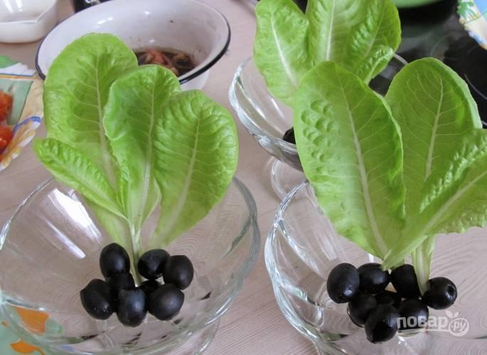Укладываем в вазочки листья салата и маслины.