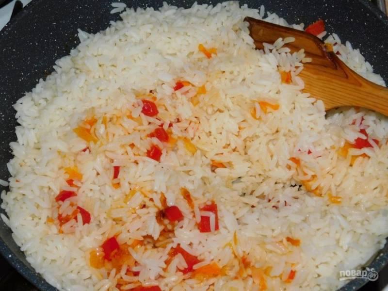 Затем содержимое сковороды смешайте с рисом. Прогрейте хорошо, добавьте соль и специи по вкусу.
