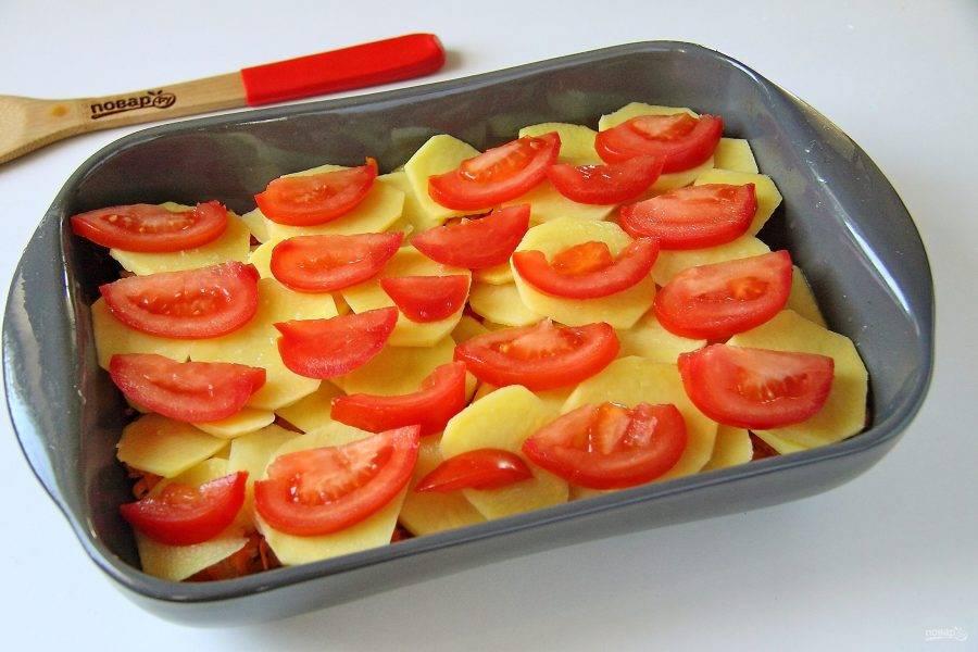Выложите оставшийся картофель, посолите его и положите нарезанные дольками помидоры.