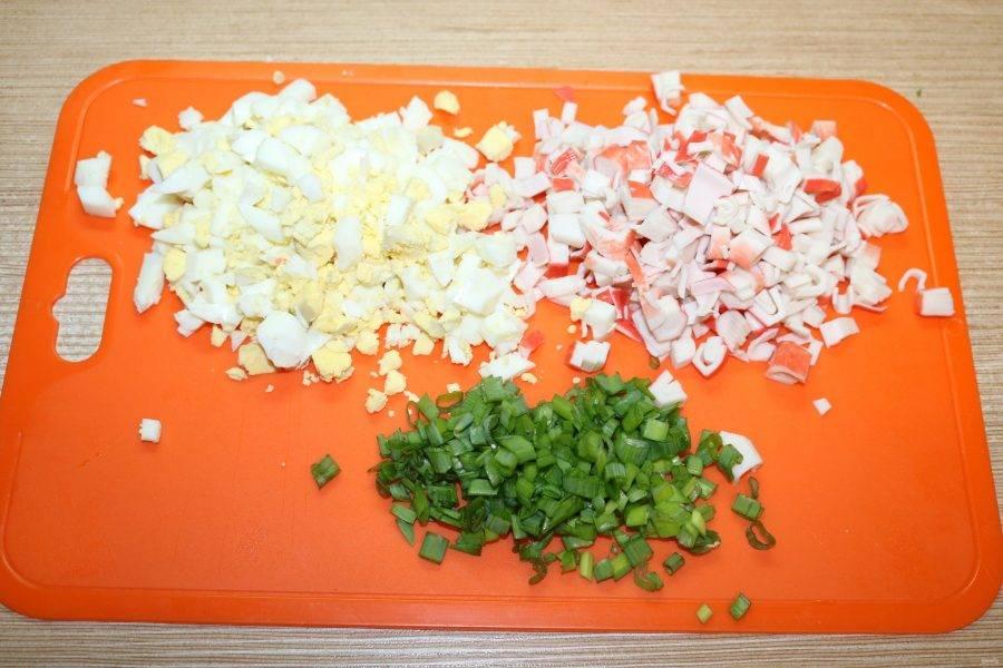 Яйца отварите до готовности. Крабовые палочки и яйца нарежьте кубиками. Зелень измельчите.