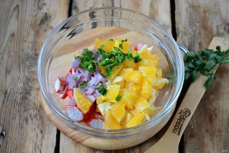 Апельсин очистите и порежьте на небольшие кусочки, смешайте с крабовыми палочками и луком. Порубите петрушку и добавьте в салат.