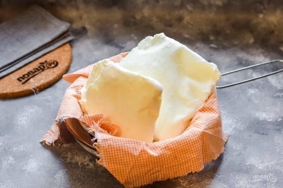 Спустя указанное время достаньте кефир и сметану, пакеты разрежьте и достаньте кефир со сметаной. Теперь сито поставьте в тарелку, застелите сито тканью или марлей. Выложите замороженный кефир и сметану в сито. Оставьте ингредиенты на 5-6 часов.
