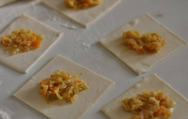 Пласты слоеного теста разрезаем на квадратики толщиной 2 мм. Смочите тесто водой, разложите на каждый квадратик начинку.