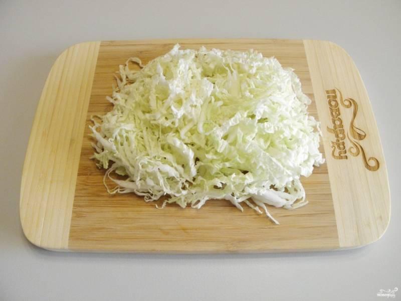 Нашинкуйте тонко капусту пекинскую.