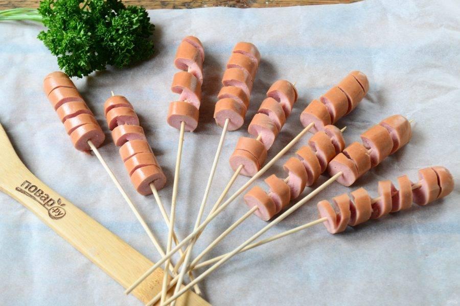 Каждую сосиску разрежьте пополам и оденьте на деревянную шпажку. Затем острым ножом сделайте надрезы по спирали, доходя до шпажки. У вас получится спираль из сосиски, максимально растяните ее.